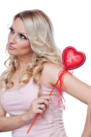 Beautiful angry blonde holding red heart with words I Love You, isolated on white Stock Photo - 17281916