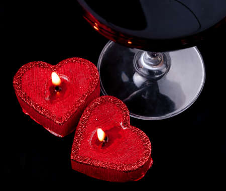 Two burning heart shape candles and wineglass on the black background Stock Photo - 17356882