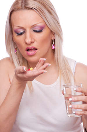 Blonde woman holding pills and glass of water photo
