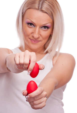 Lovely blonde knocking red Easter eggs, isolated on white photo