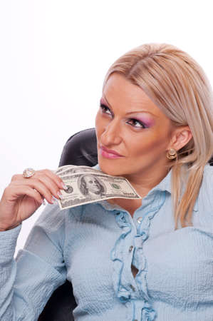 Beautiful blonde sitting in the office chair, holding American Dollar bills and thinking photo
