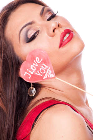 Beautiful brunette holding heart shape lollipop with words I Love You photo