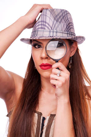 Lovely brunette with hat looking through a magnifying glass, isolated on white photo