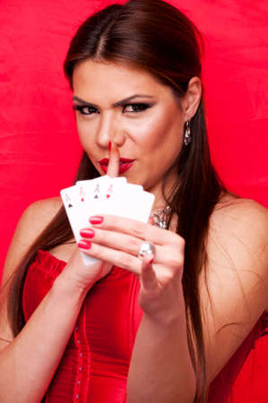 Attractive brunette holding four aces and showing shush sign with index finger on her lips, on the red background photo