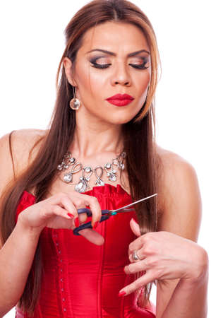 Attractive brunette in red coset cutting her own hair, isolated on white Stock Photo - 18008673