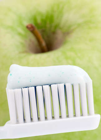 Macro shot of toothpaste on the toothbrush with green apple in the background photo