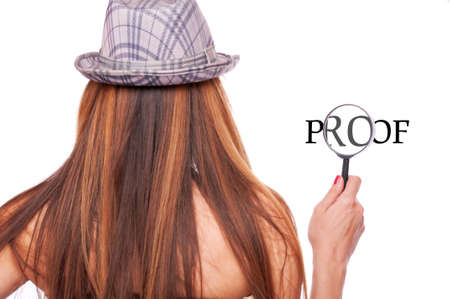 Long hair brunette with hat holding loupe and magnifying word proof photo