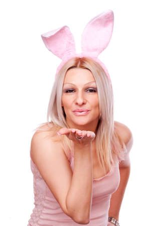 Attractive blonde with rabbit ears send kiss, isolated on white photo