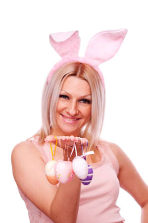 Beautiful blonde with bunny ears and hanging decorative Easter eggs on the fingers, isolated on white photo