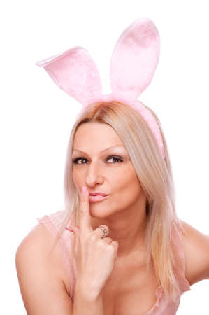 Beautiful blonde with bunny ears holding index finger on her lips photo