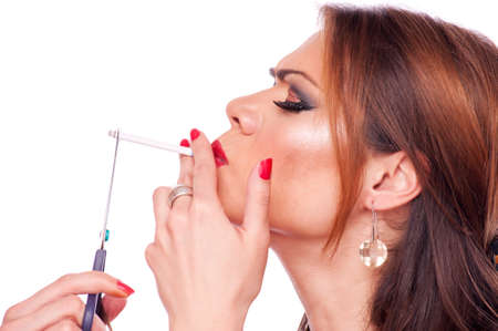 quiting: Profille image of a beautiful brunette cuts a cigarette with scissors Stock Photo