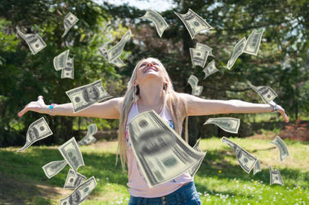 happy shopper: Beautiful blonde with outstretched hands wait for American hundred Dollar bills which fall from the sky, in the park Stock Photo