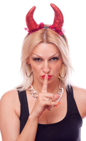 Pretty blonde woman with devil red horns making a hush gesture, isolated on white photo