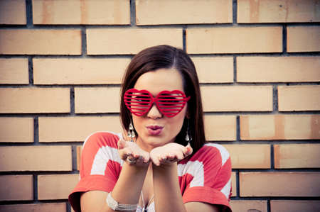 Cute young woman with heart-shape eyeglasses sending kiss, with yellow brick wall in the background photo