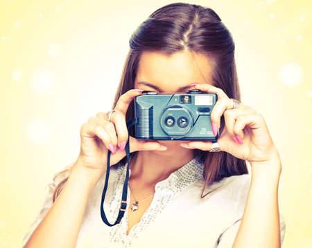 Young woman with old camera on the yellow background photo