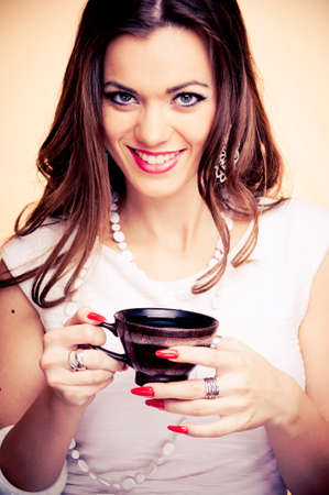 Beautiful brunette holding cup of coffee, with beige background photo