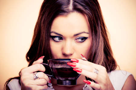 Beautiful young brunette drinking coffee, on the beige background photo