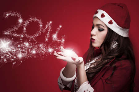 Beautiful brunette in the Santa costume blowing snowflakes and make New Year numbers 2014 photo