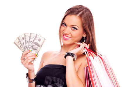 Beautiful brunette holding American hundred Dollar bills and shopping bags over shoulder, isolated on white photo