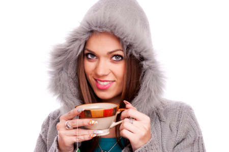 Young brunette in the gray sweater with hood drinking hot tea - isolated on white photo