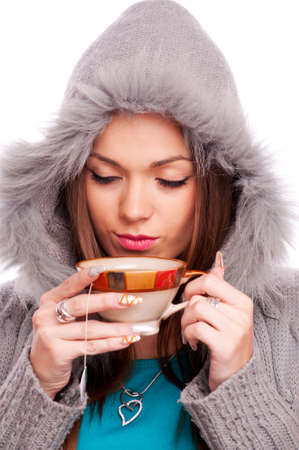 Young brunette with closed eyes, holding a cup of hot tea - isolated on white photo