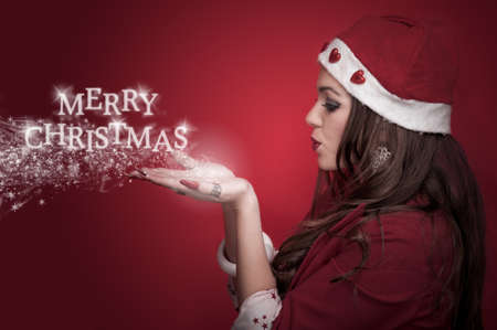 Profile of a beautiful brunette in the Santa costume blowing snowflakes and make words Merry Christmas photo