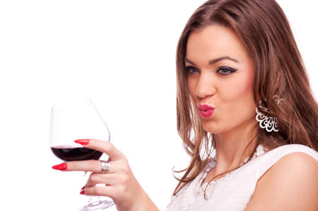 Young beautiful brunette holding glass of red wine and sending kiss with lips, isolated on white photo