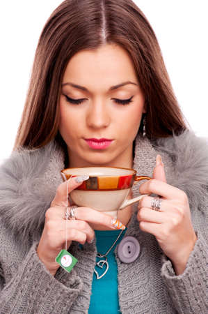 Young brunette with closed eyes, holding hot tea - isolated on white photo