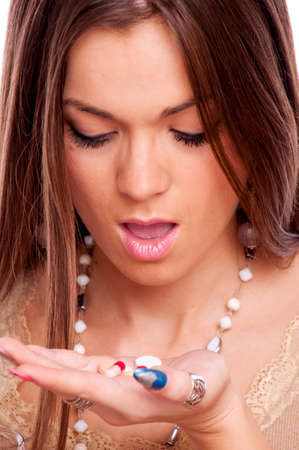 Brunette with open mouth holding medicine on the palm photo