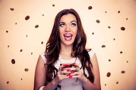 Thrilled beautiful brunette holding cup of coffee while coffee beans falling around her, with beige background photo