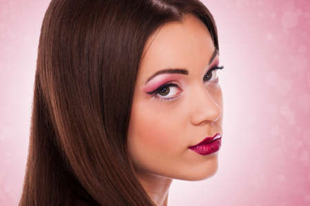 Portrait of beautiful woman with makeup on the pink background with circles  photo