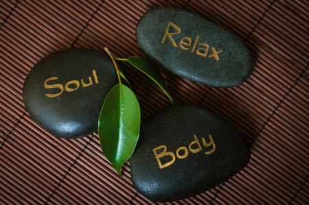 Three black massage stone with words Body, Soul and Relax photo