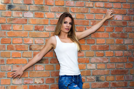 arm: Young girl in a white t-shirt with outstretched arms posing next to a brick wall Stock Photo