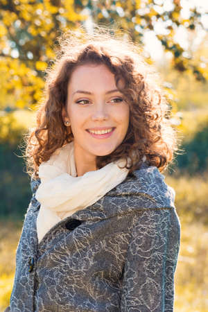 adult young: Beautiful young woman with curly hair posing in the front of blurred yellow leaves