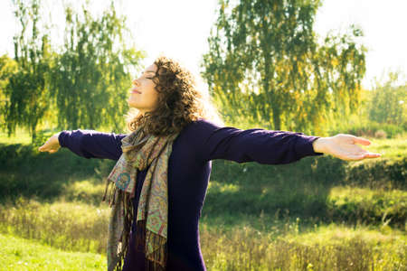 waist deep: Young woman with outstretched hands enjoying outdoors Stock Photo