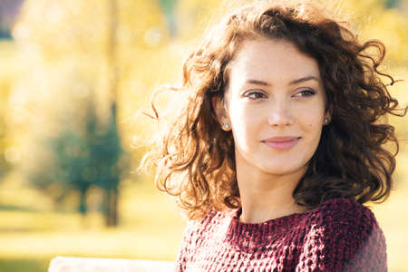 white women: Beautiful young woman with curly hair posing outdoors at autumn