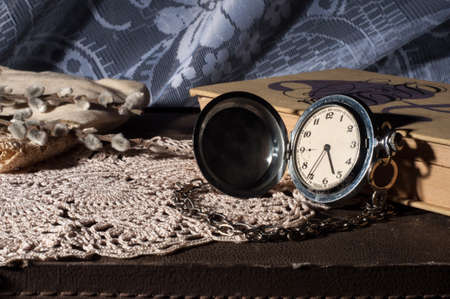 Vintage book and pocket watch on an old suitcase