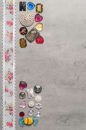 multi-colored sewn stones on a grey background.Copy Space