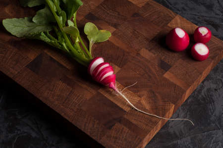 Radish on a wooden board on a dark background 版權商用圖片