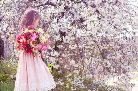 Adorable little girl holding flowers for her mother in blooming cherry garden on beautiful spring day
