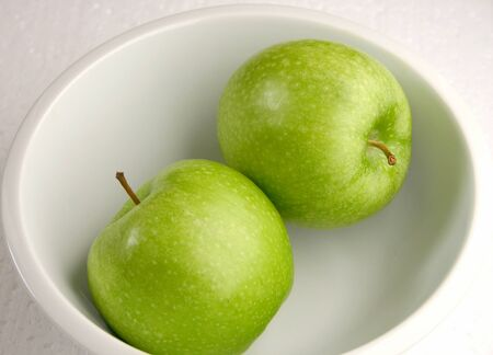 Two bright green apple in a dish photo