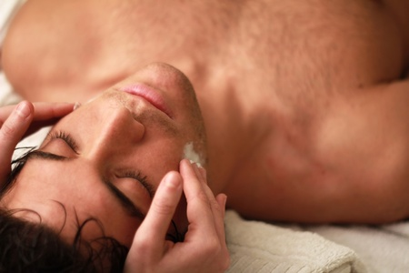 Young man relaxing during a massage with eyes shut photo