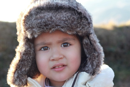 meaningful: Wonderful portrait of a little child with fur hat and  intense gaze