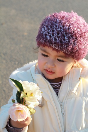 coif: Adorable child with wool coif looking at flowers in sunset light Stock Photo