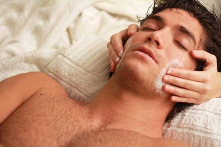 homme massage: Massage relaxant du visage à un beau jeune homme à la station thermale