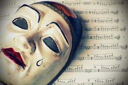 Pierrot mask over written music . Retro styled.