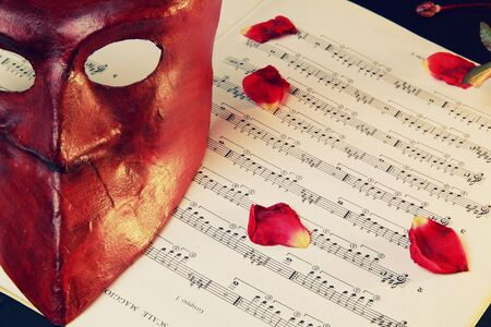 Venetian mask over music score and rose petals in candle light . Retro styled  photo