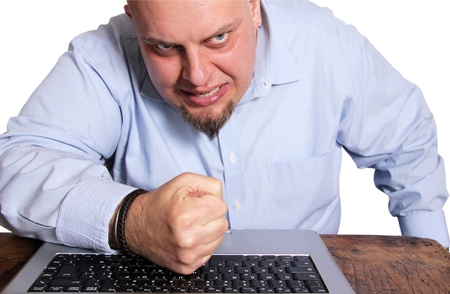 destruct: Angry man in front of computer  giving a punch to keyboard