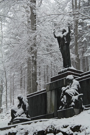 Gothic mausoleum statues in woodland covered by snow photo