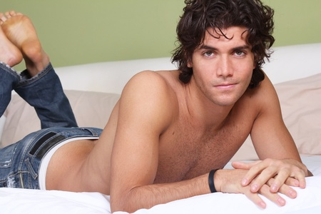 Handsome young man with jeans on bed looking at camera
